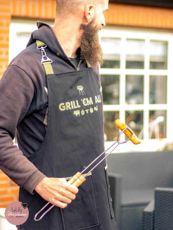 """Mann grillt mit Schürze auf der """"Grill 'em all"""" steht"""