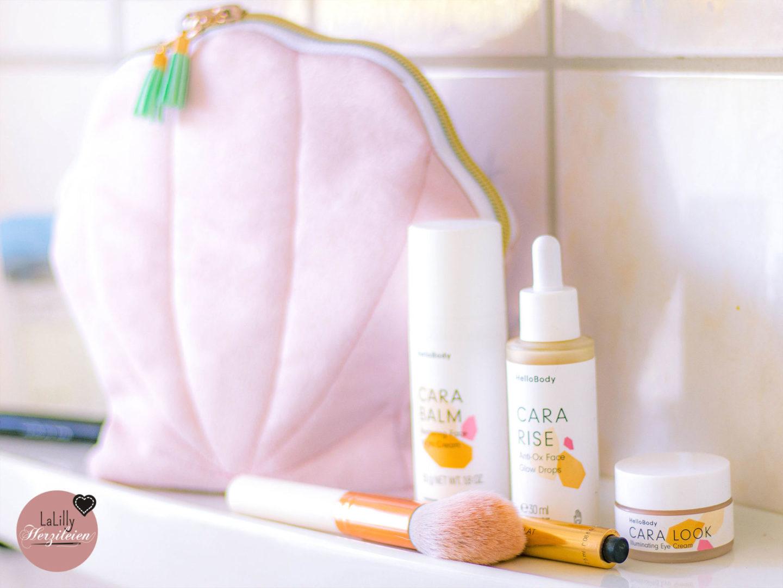 HelloBody Produkte aus der Cara Serie neben einer Kosmetiktasche in Muschelform